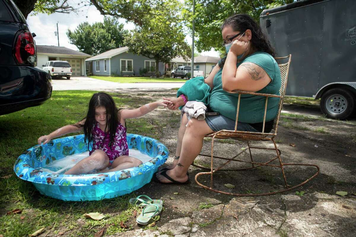 Diana Gonzalez sits outside her house watching her daughter, Maddilyn, play in her baby pool Monday, July 19, 2021 in Galena Park. Gonzalez was one of the area residents who reported concerning smells in Galena Park starting July 14, but two days passed before they learned what it was.