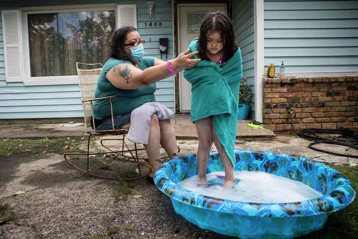 Diana Gonzalez wraps a towel around her daughter, Maddilyn, as she sits outside her house watching her play in her baby pool Monday, July 19, 2021 in Galena Park. Gonzalez was one of the area residents who reported concerning smells in Galena Park starting July 14, but two days passed before they learned what it was.