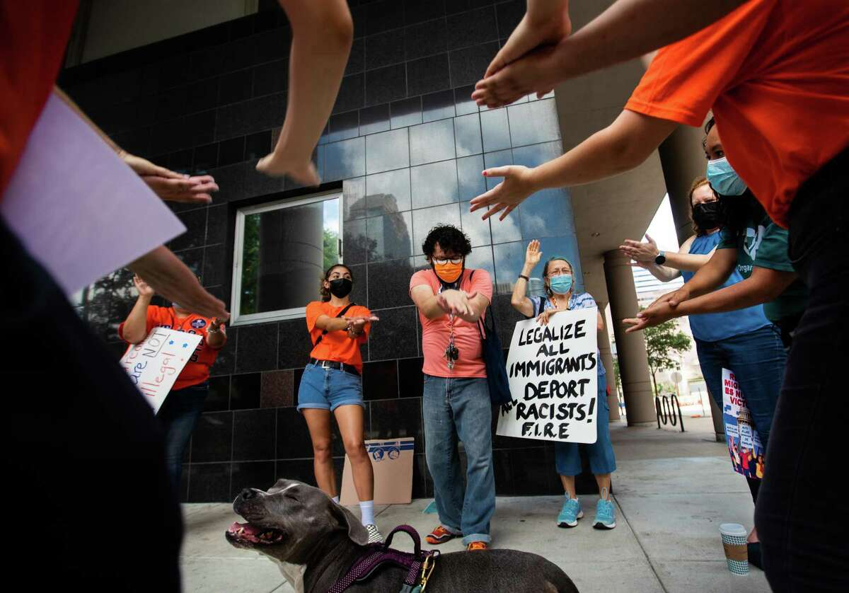 """Immigrant youths and allies end a protest on a DACA ruling by doing a """"unity clap"""" and chanting """"Isang Bagsak,"""" to symbolize solidarity in Tagalog, at the downtown U.S. District Court building."""