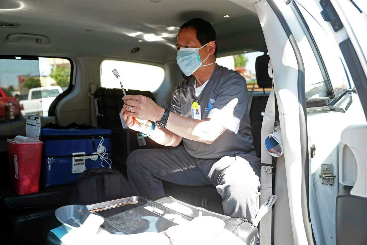 Pharmacist Richard Ko readies a vaccine shot inside Contra Costa Health Services' mobile health van at Cielo Market in Antioch.