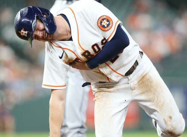 Houston Astros right fielder Chas McCormick (20) reacts to getting hit by a ball while sliding back to first base in the fourth inning at Minute Maid Park on Monday, July 19, 2021. Houston Astros host Cleveland Indians for a three-game series. Photo: Elizabeth Conley/Staff Photographer / © 2021 Houston Chronicle