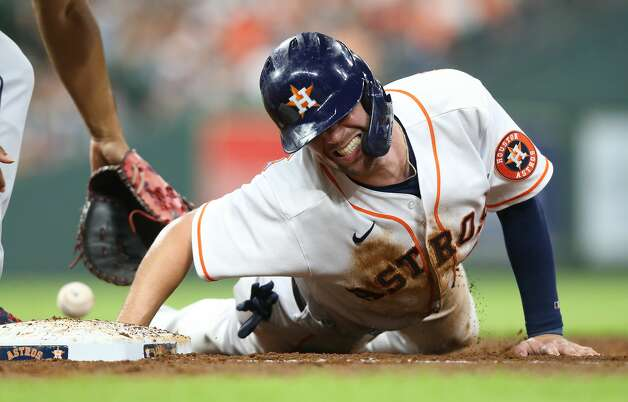 Houston Astros right fielder Chas McCormick (20) reacts to getting hit by a ball while sliding back to first base under Cleveland Indians first baseman Bobby Bradley (44) at Minute Maid Park on Monday, July 19, 2021. Houston Astros host Cleveland Indians for a three-game series. Photo: Elizabeth Conley/Staff Photographer / © 2021 Houston Chronicle