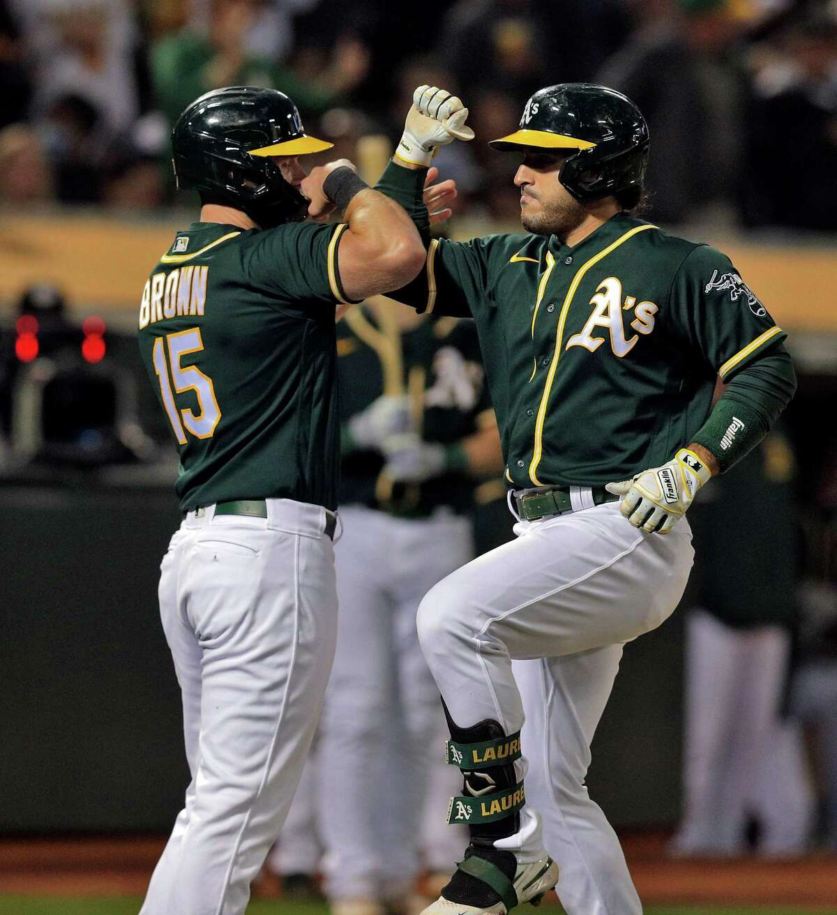 Ramon Laureano (22) gets a high five from Seth Brown (15) after they both scored on Laureano's three run homerun in the seventh inning as the Oakland Athletics played the Los Angeles Angels at the Coliseum in Oakland, Calif., on Monday, July 19, 2021.