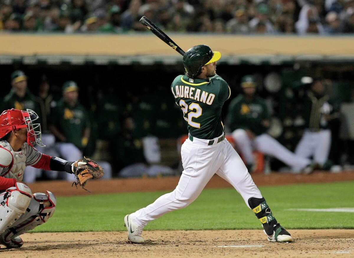 Ramon Laureano (22) watches the flight of his three run homerun in the seventh inning off reliever Steve Cishek (40) as the Oakland Athletics played the Los Angeles Angels at the Coliseum in Oakland, Calif., on Monday, July 19, 2021.