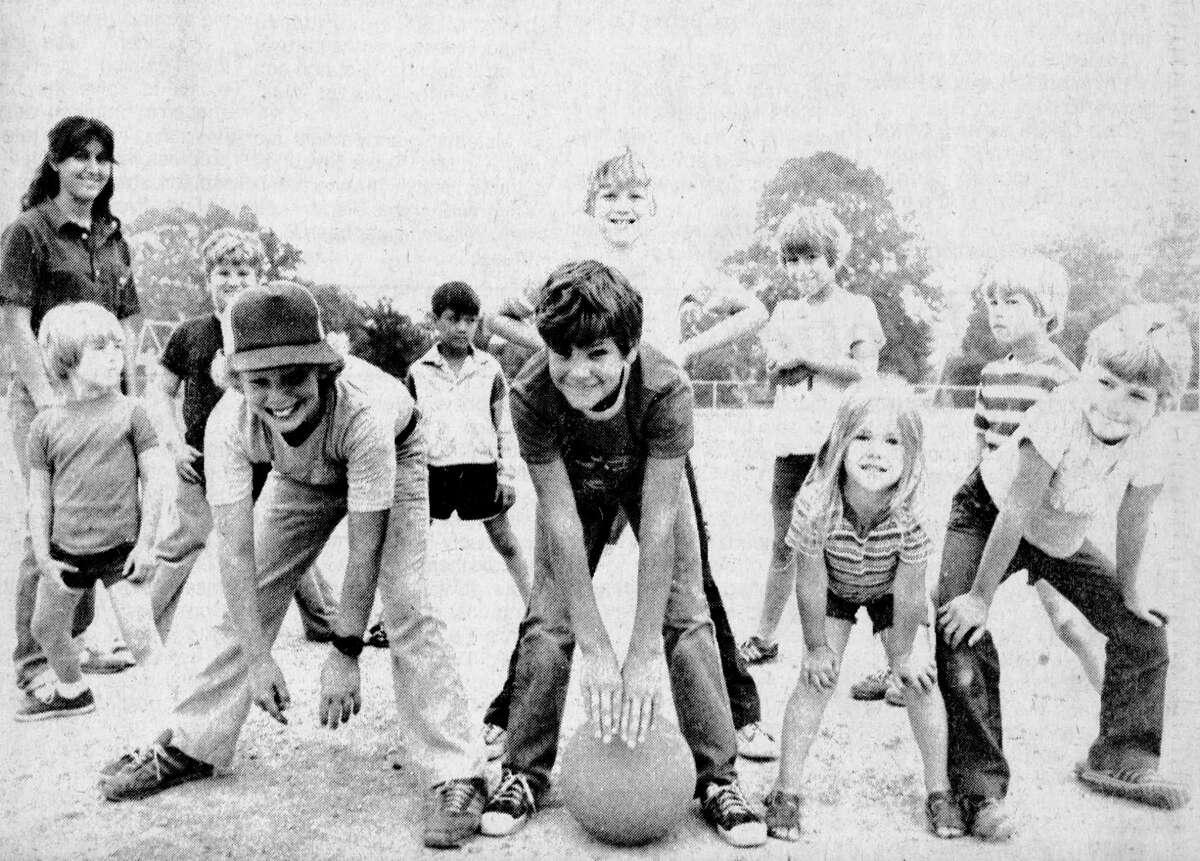 (From left) Tammy Ledford supervises a game of Human Pinball with a group of youngsters who are participating in the Manistee Recreation Association's summer playground program. This group was caught in the middle of their game at Lincoln School's playground. (From left, front row) Julie Patulski, Forrest Green, Scott Misico, Scott Cabot, Cheryl Dalke and Scott Daughtery. (From left, back row) Shawn Cabot, Kevin Niemiec, Susan Niemiec, Sean Dalke and Eric Dalke. The photo was published in the July 20, 1981 issue of the News Advocate. (Manistee County Historical Museum photo)