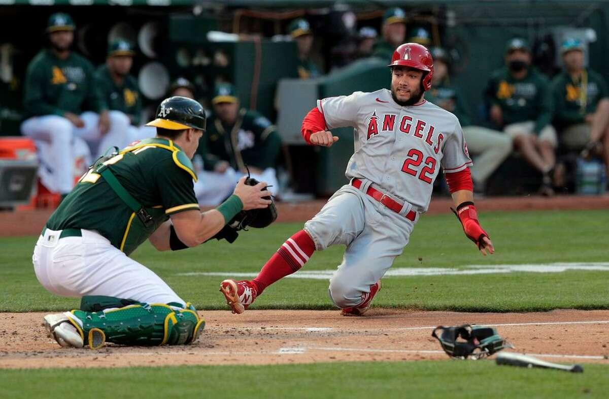 David Fletcher (22) is tagged out at the plate by Sean Murphy (12) while trying to score on a double hit by Shohei Ohtani (17) in the third inning as the Oakland Athletics played the Los Angeles Angels at the Coliseum in Oakland, Calif., on Monday, July 19, 2021.
