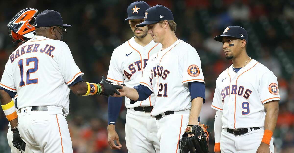 Houston Astros manager Dusty Baker Jr. (12) takes the game ball from Houston Astros starting pitcher Zack Greinke (21) in the sixth inning against the Cleveland Indians at Minute Maid Park on Monday, July 19, 2021. Houston Astros host Cleveland Indians for a three-game series.