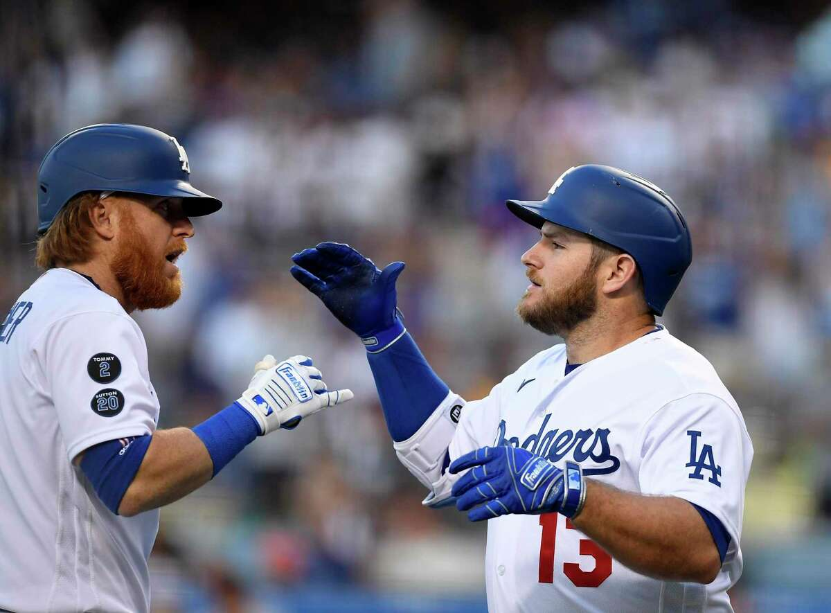 LOS ANGELES, CA - JULY 19: Max Muncy #13 of the Los Angeles Dodgers is congratulated by Justin Turner #10 of the Los Angeles Dodgers after hitting a one run home run against pitcher Kevin Gausman #34 of the San Francisco Giants during the first inning at Dodger Stadium on July 19, 2021 in Los Angeles, California. (Photo by Kevork Djansezian/Getty Images)