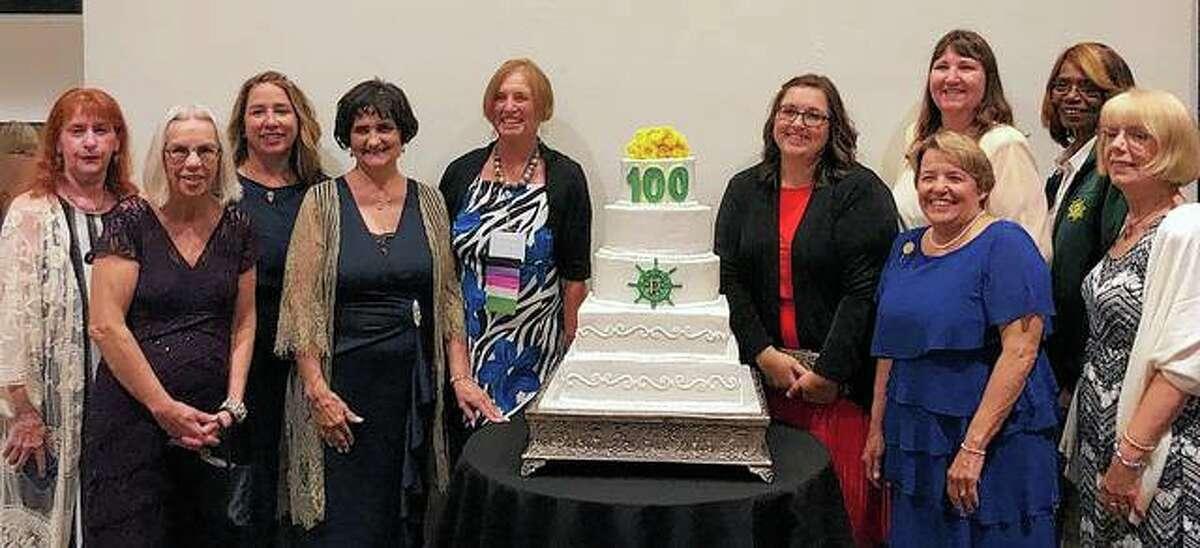 Members of the Pilot Club of Jacksonville flank a cake celebrating Pilot International's 100th anniversary.