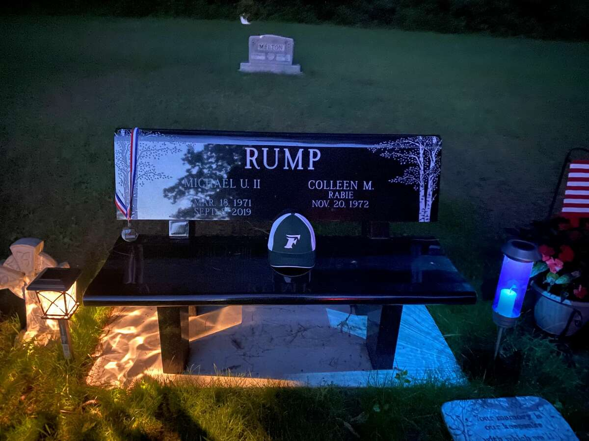 Liam Rump's hat and district championship medal are seen on the memorial bench and head stone at his father Michael's grave site.