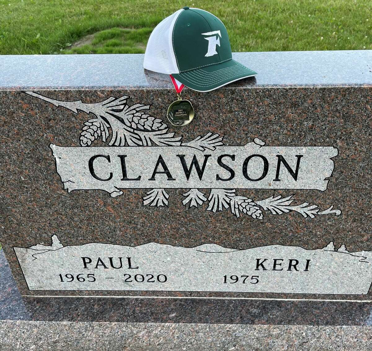 Jacob Clawson's hat and district championship medal are seen on the head stone of his father Paul's grave site.
