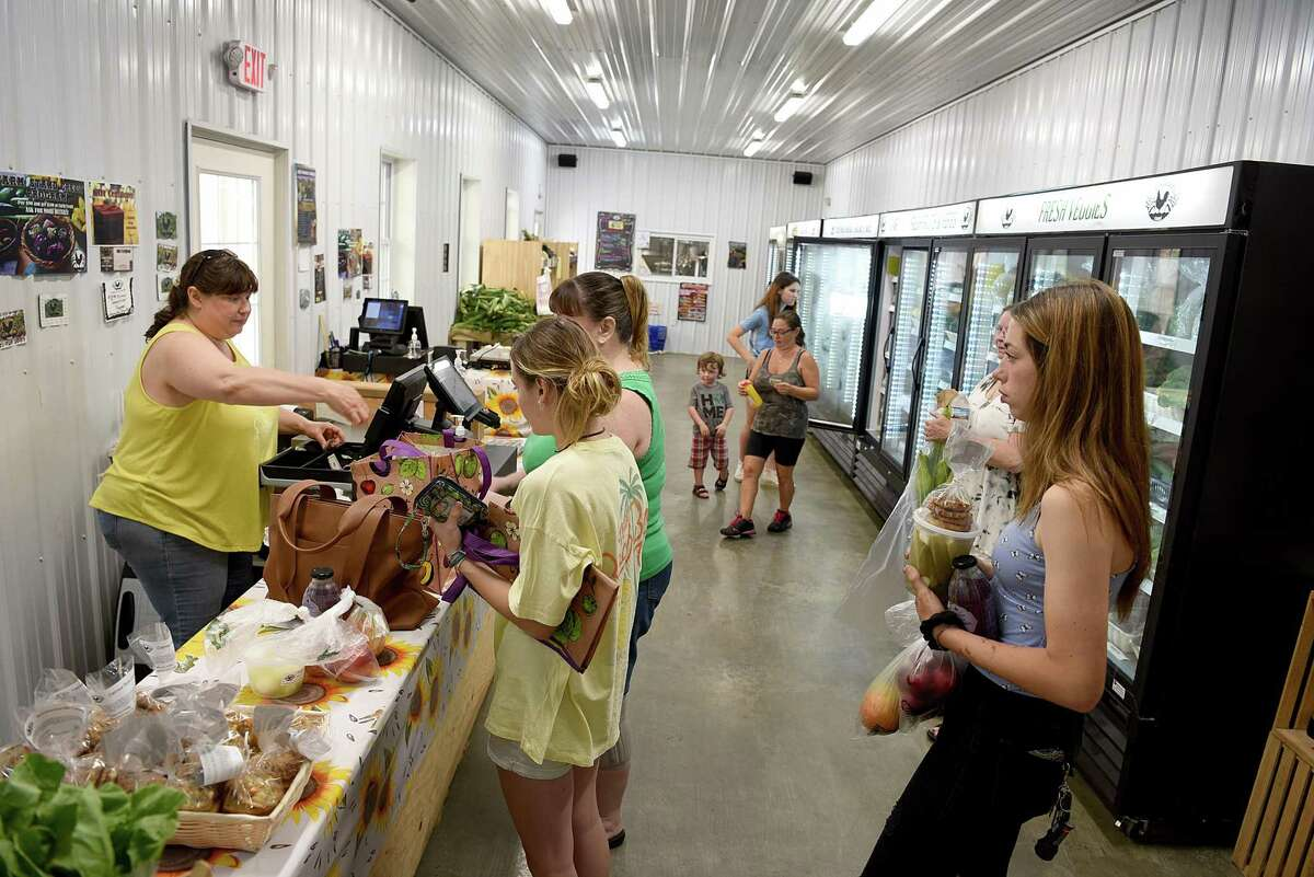 Stacia Monahan, left, on the register, services customers at the farm store at Stone Gardens Farms in Shelton, Ct.,Saturday, July 17, 2021.