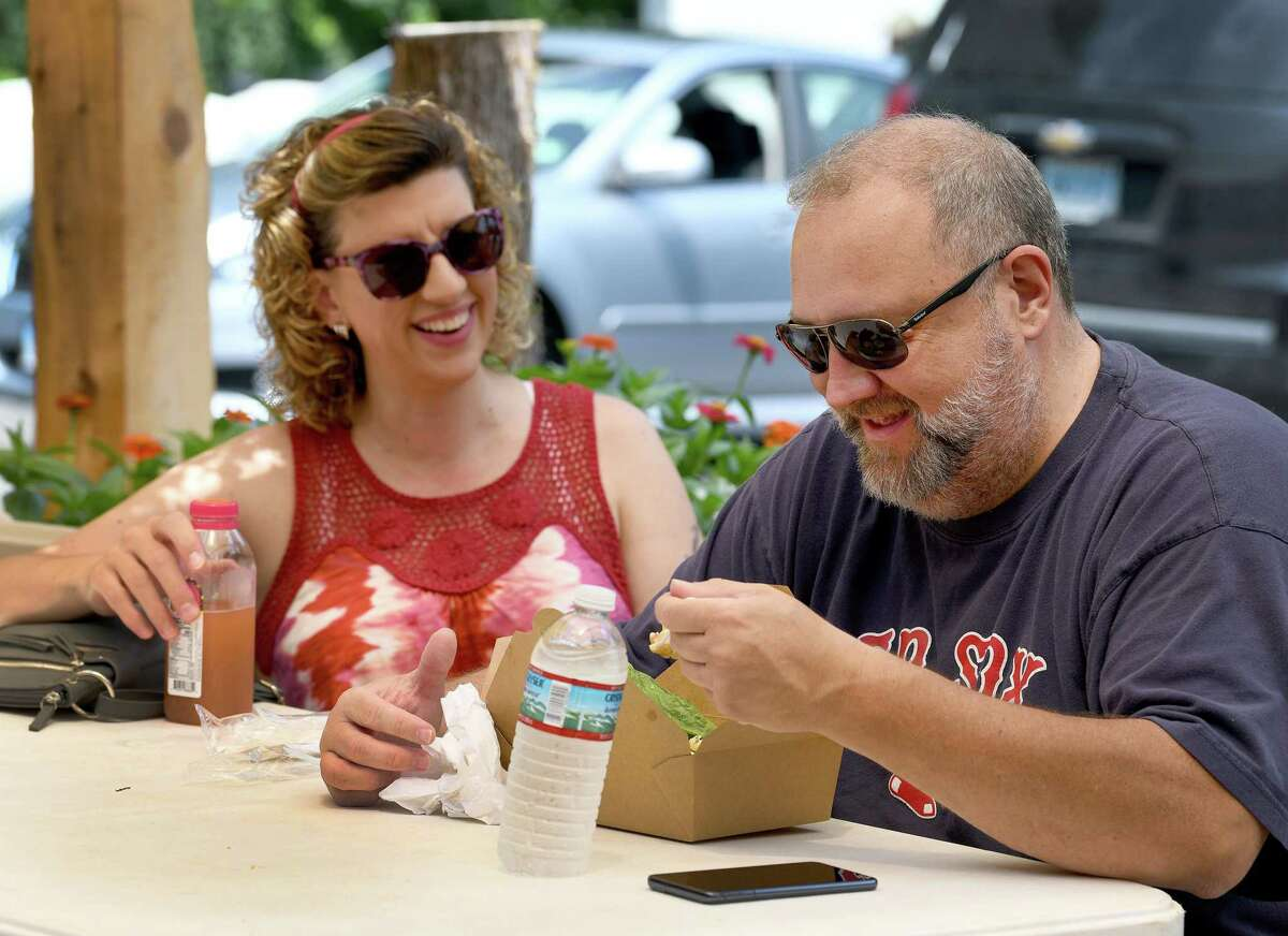 Melissa Kross, left, and Eric Carpenter enjoy kielbasa sandwiches for lunch at Stone Gardens Farms in Shelton, Ct. Saturday, July 17, 2021.