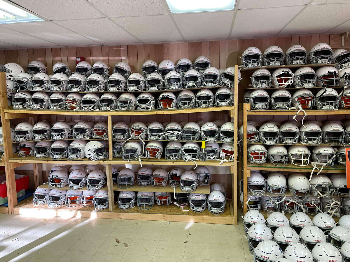 Dozens of Riddell SpeedFlex helmets sit on shelves in the Midland Area Youth Football League's storage unit.