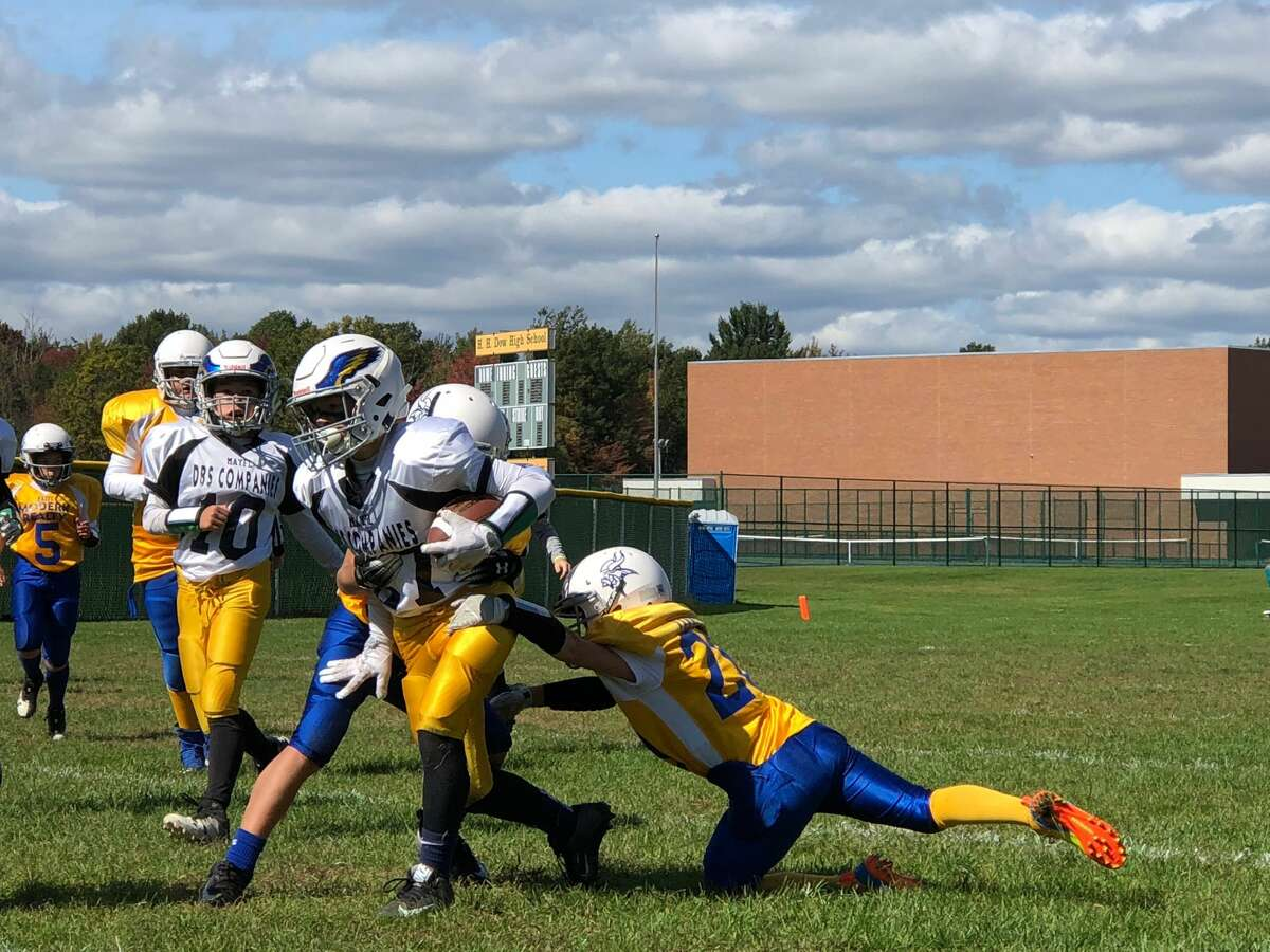 The ballcarrier breaks a tackle during a Midland Area Youth Football League game on an unspecified date.