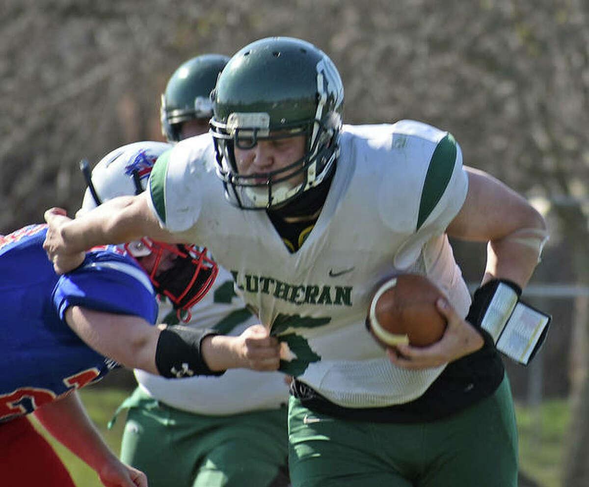 Metro-East Lutheran quarterback Erik Broekemeier breaks a tackle from Pawnee defender during the second half on April 3 in Pawnee.