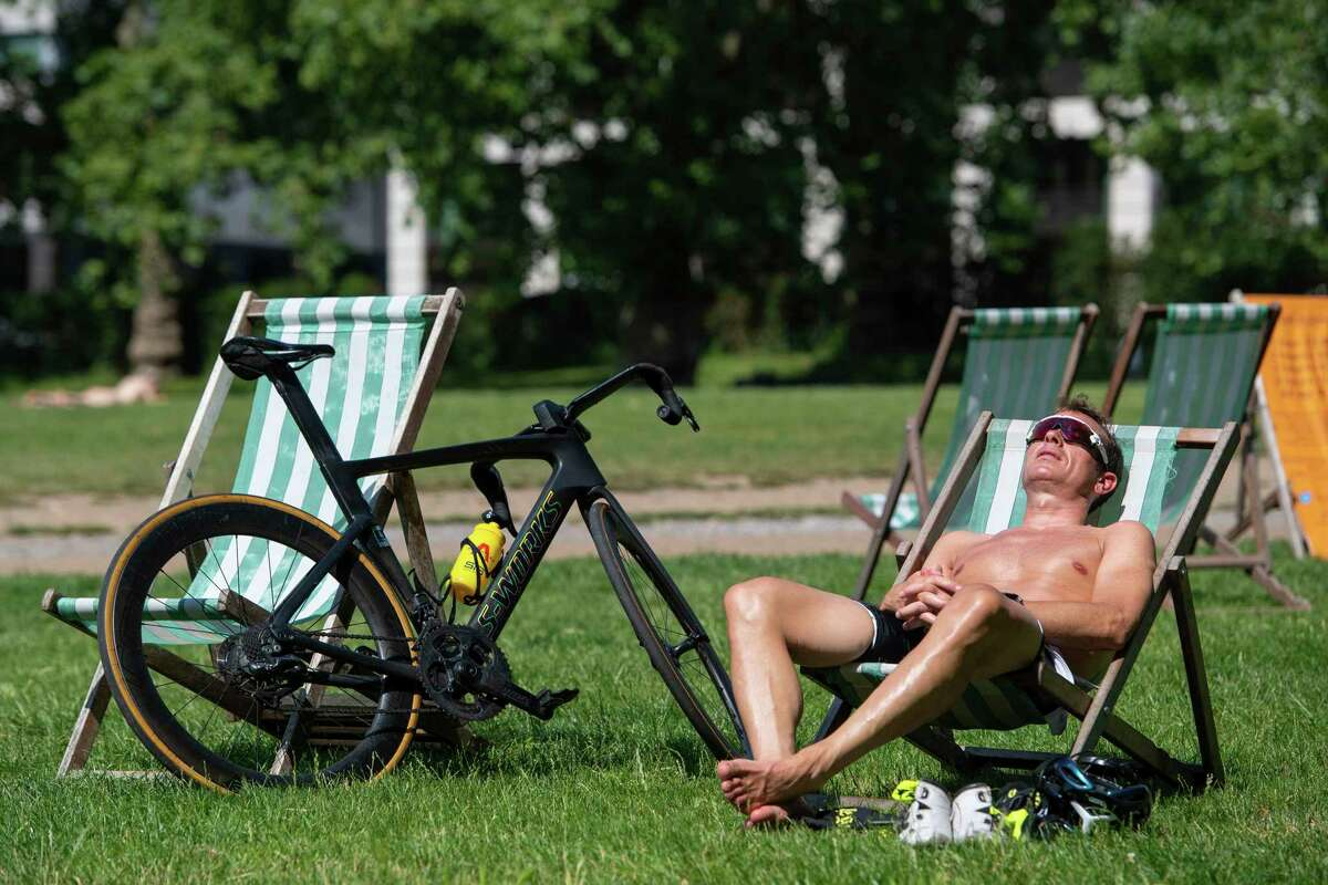 A man relaxes in the morning sunshine during a spell of hot weather in Green Park central London, Tuesday July 20, 2021. Temperatures are set to soar to sweltering highs this week according to weather forecasts, and the Met Office issued an unprecedented heat warning. (Dominic Lipinski/PA via AP)
