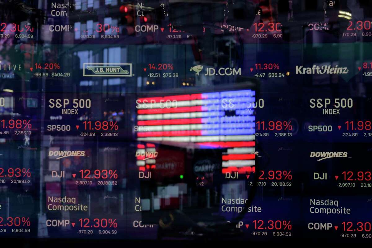 FILE - In this March 16, 2020 file photo, a United States flag is reflected in the window of the Nasdaq studio, which displays indices and stocks down, in Times Square, New York. Many U.S. companies have rushed to appoint Black members to their board of directors since racial justice protests swept the country last year. But in the two preceding years, progress on increasing racial diversity on boards stagnated, a new study revealed Tuesday, June 8, 2021. Nasdaq filed a proposal with the Security and Exchange Commission to adopt new listing rules requiring companies to publicly disclose their board diversity statistics. (AP Photo/Seth Wenig, File)