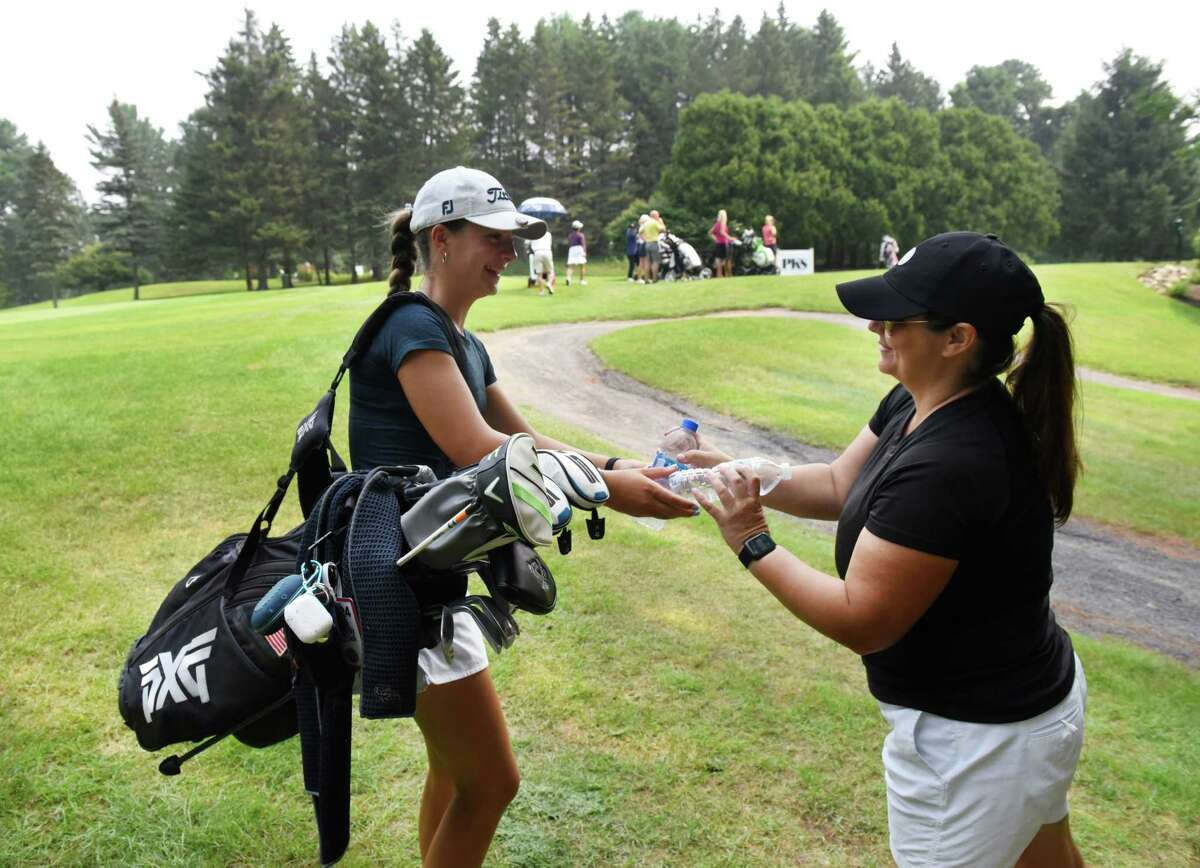 Symetra Tour golfer Kennedy Swedick, 14, of Altamont, left, trades water bottles with her mother, Karen, during a practice round on Tuesday, July 20, 2021, at Pinehaven Country Club in Guilderland, N.Y. She is playing in the Twin Bridges Championship on a sponsor's exemption. (Will Waldron/Times Union)