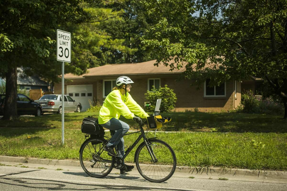 Midland County Mosquito Control employee Jenni Lewis of Coleman rides from one water catch basin to the next, dropping mosquito growth regulator pellets into each one, Tuesday, July 20, 2021 in Midland. (Katy Kildee/kkildee@mdn.net)