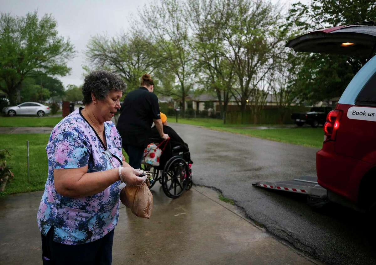 Mary Morris pushes one of her clients toward a taxi cab before going to a doctor's appointment March 20, 2020, in South Houston, Texas. Door-to-door services for the elderly and disabled are a critical link, but drivers say cab companies and transit officials have skirted employee laws by declaring them independent contractors.