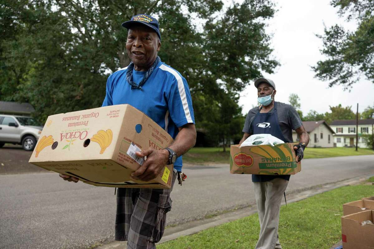 Henry Caylen, left and Sherman Benoit carry boxes of food out to vehicles during a food pantry pick-up event at Pilgrim Rest Baptist Church, Tuesday, July 20, 2021, in Conroe.