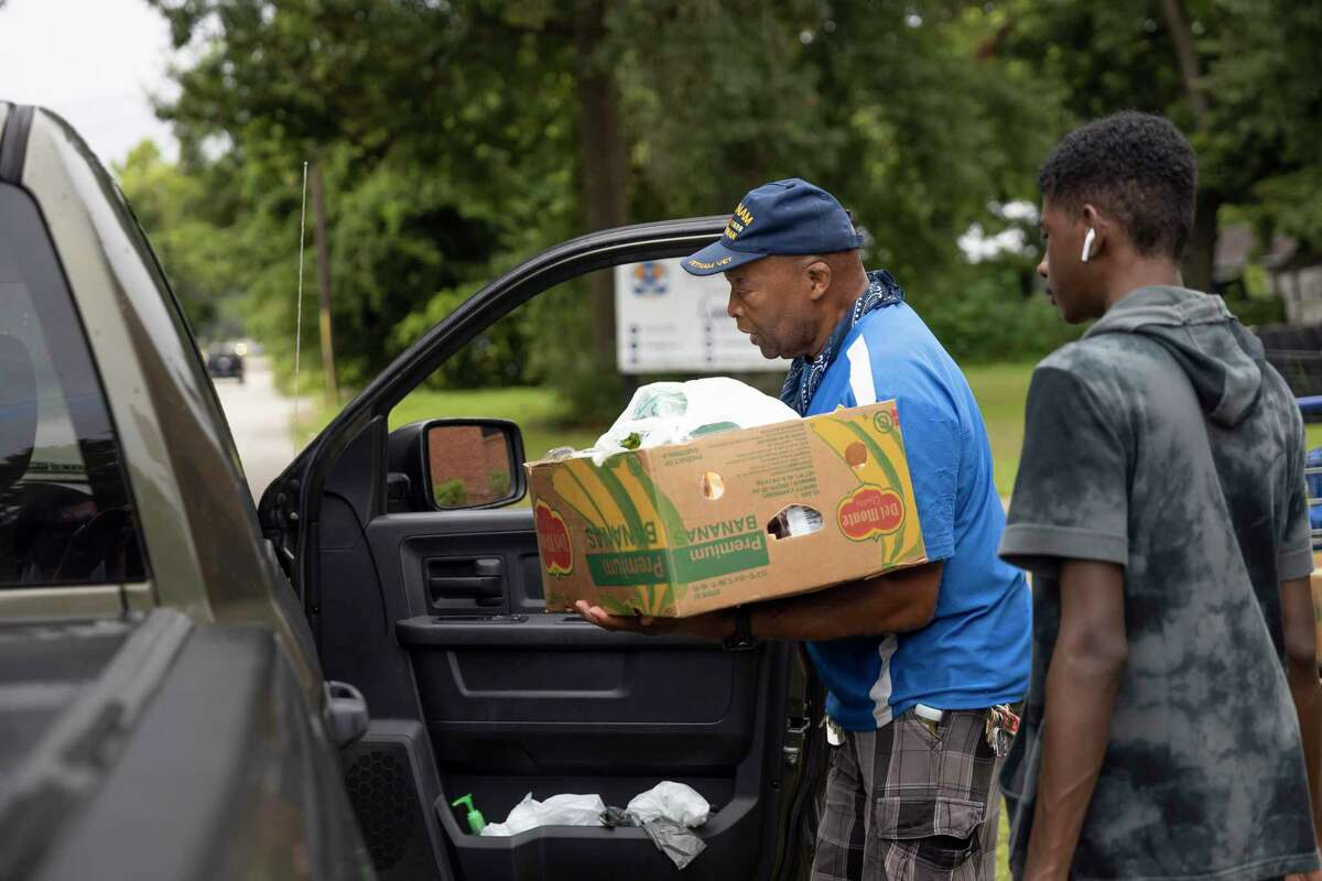 Henry Caylen, center, loads a box of food into a cake during a food pantry pick-up event at Pilgrim Rest Baptist Church, Tuesday, July 20, 2021, in Conroe.