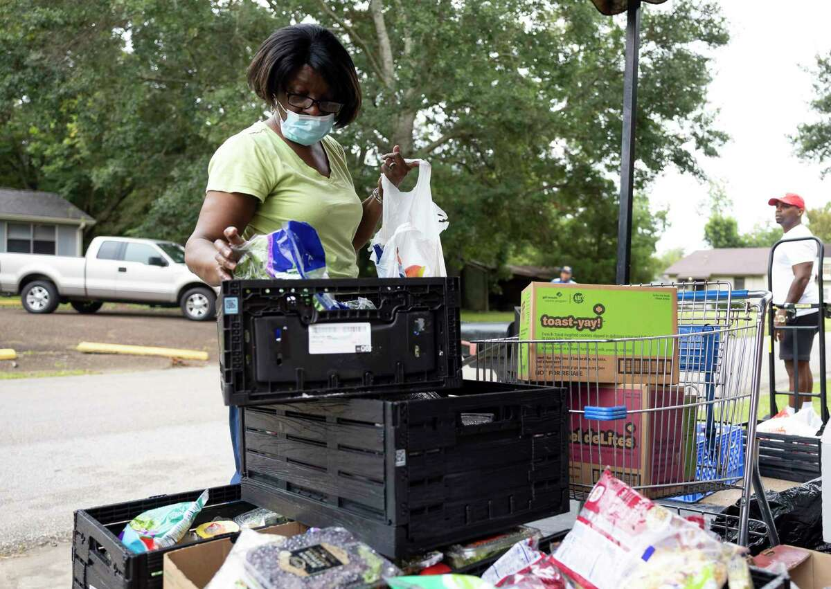 Frances Harris prepares a bag of food during a food pantry pick-up event at Pilgrim Rest Baptist Church, Tuesday, July 20, 2021, in Conroe.