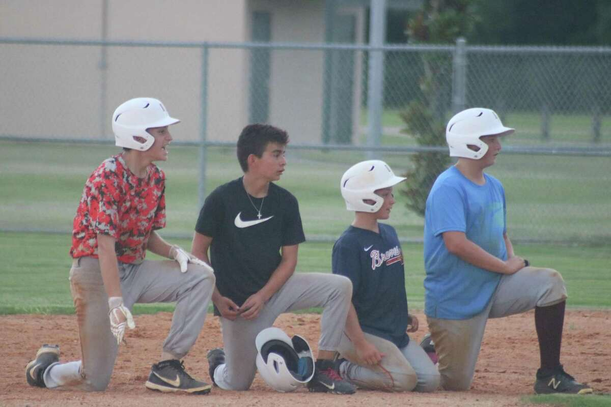 Four members of the Deer Park Bronco all-stars wait their turn to run a drill at the Ruth Minchen Athletic Complex Monday night.