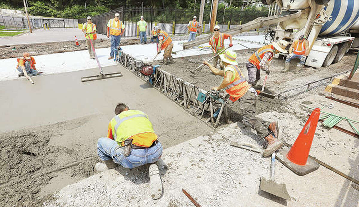 Construction workers lay fresh concrete on Williams Street in downtown Alton Tuesday. The street will eventually get its historic bricks placed back on top of the concrete. The Williams Street work is among a collection of city projects bringing improvements to all seven of the city's wards.