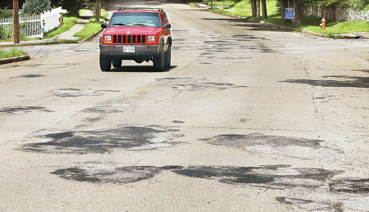 A Jeep passes through the 700 block of Union Street in Alton on Tuesday and over patch upon patch placed over the years. Union Street, one of the bumpiest streets in the city, is on a list of projects that will be taking place across the city.