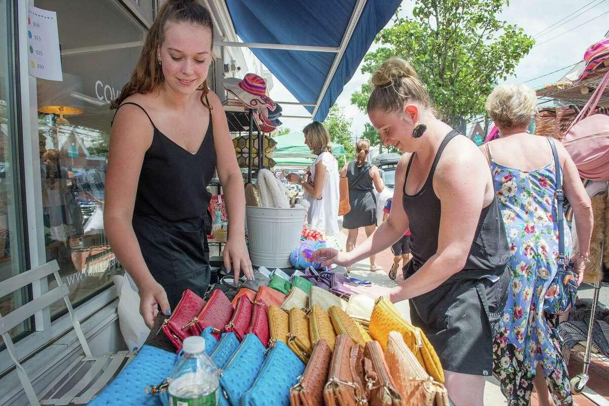 Ali Wheeler and Amanda Dervan of Kirby & Co. arrange handbags at the Darien Sidewalk Sales on Friday, July 12, 2019.