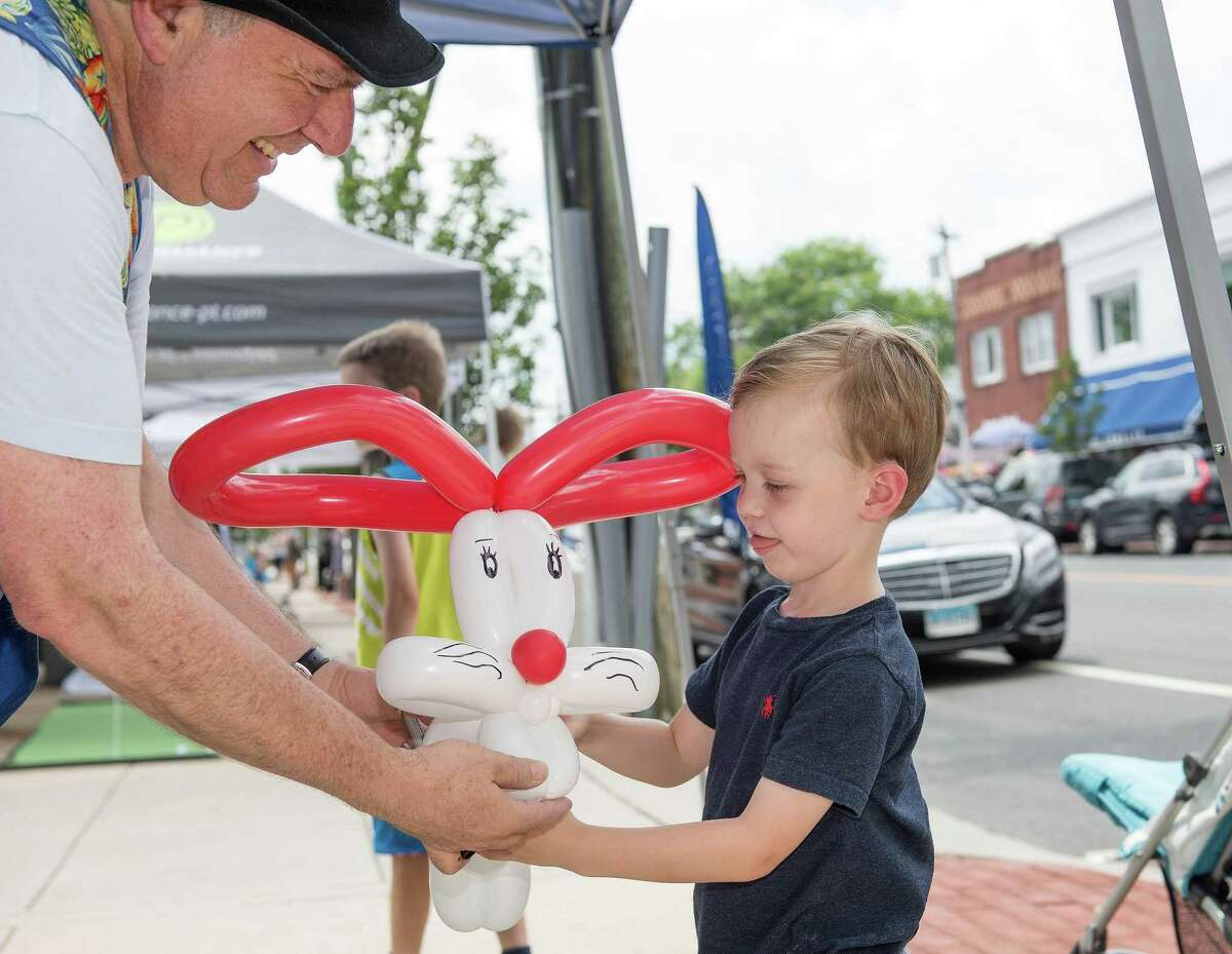 4-year-old James Baird of Darien receives a balloon bunny from Mr. Bungles at the Darien Sidewalk Sales on Friday, July 12, 2019