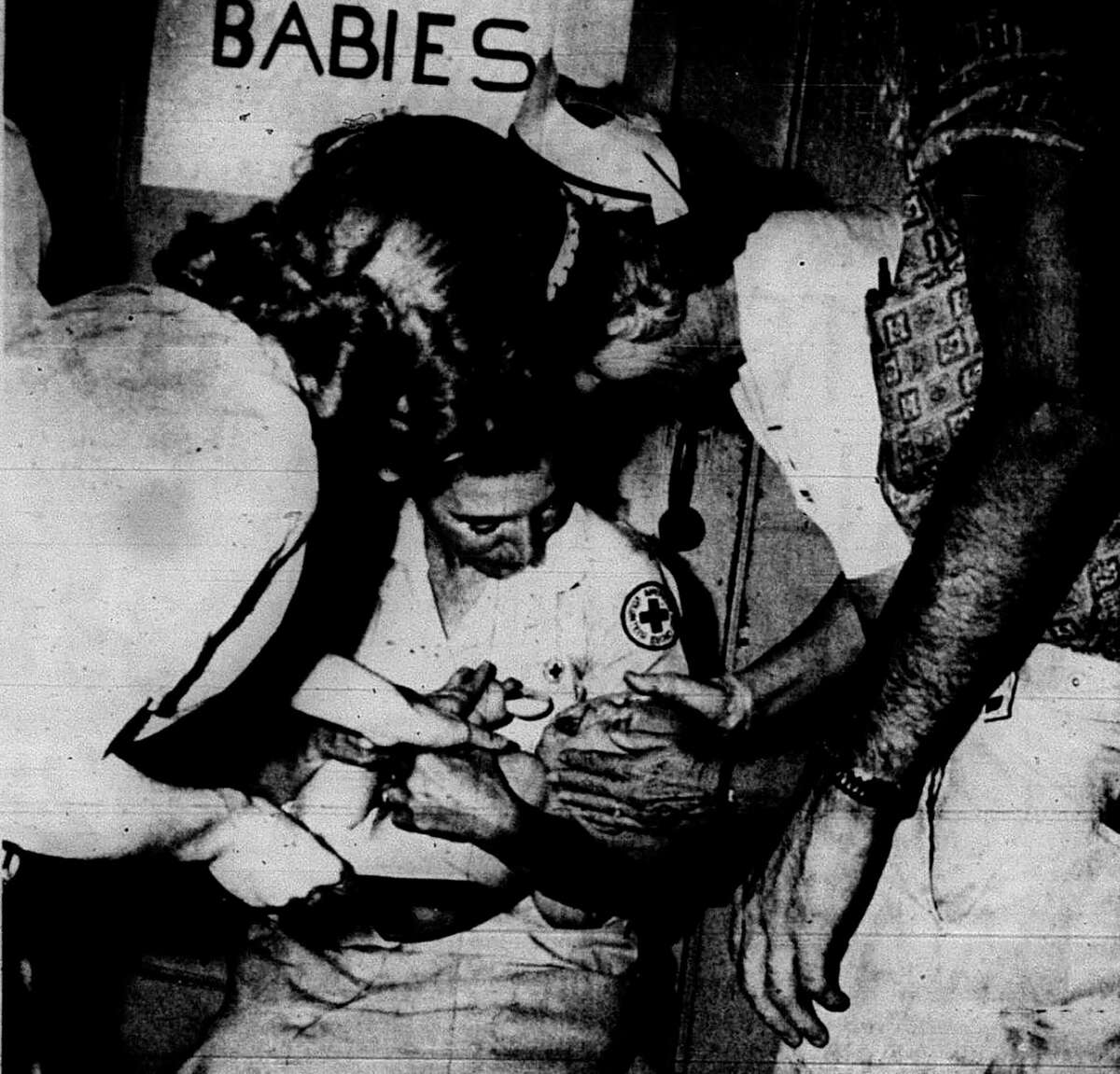 Roger McDonald, 2, receives the Sabin oral vaccine from Mrs. Hursel Long of the Grey Ladies Association during vaccinations for Polio in Conroe in 1962.