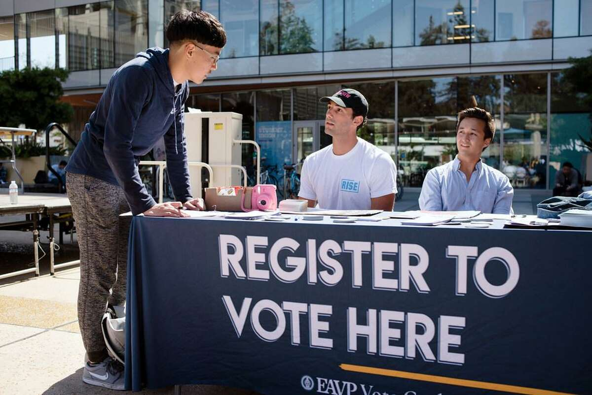 VoteCrew creator and Rise California member Maxwell Lubin (center) and Berkeley City Council candidate Rigel Robinson help Cal student Harry Lee register to vote during a VoteCrew event during National Voter Registration Day on Sept. 25, 2018, on the UC Berkeley campus.