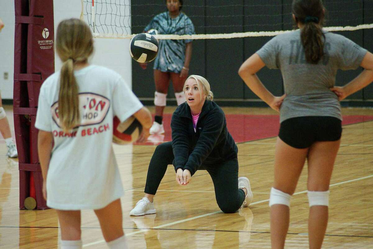 Pearland High School volleyball coach Jamie Gill demonstrates a technique during her volleyball camp on Tuesday at Pearland Junior High School South.