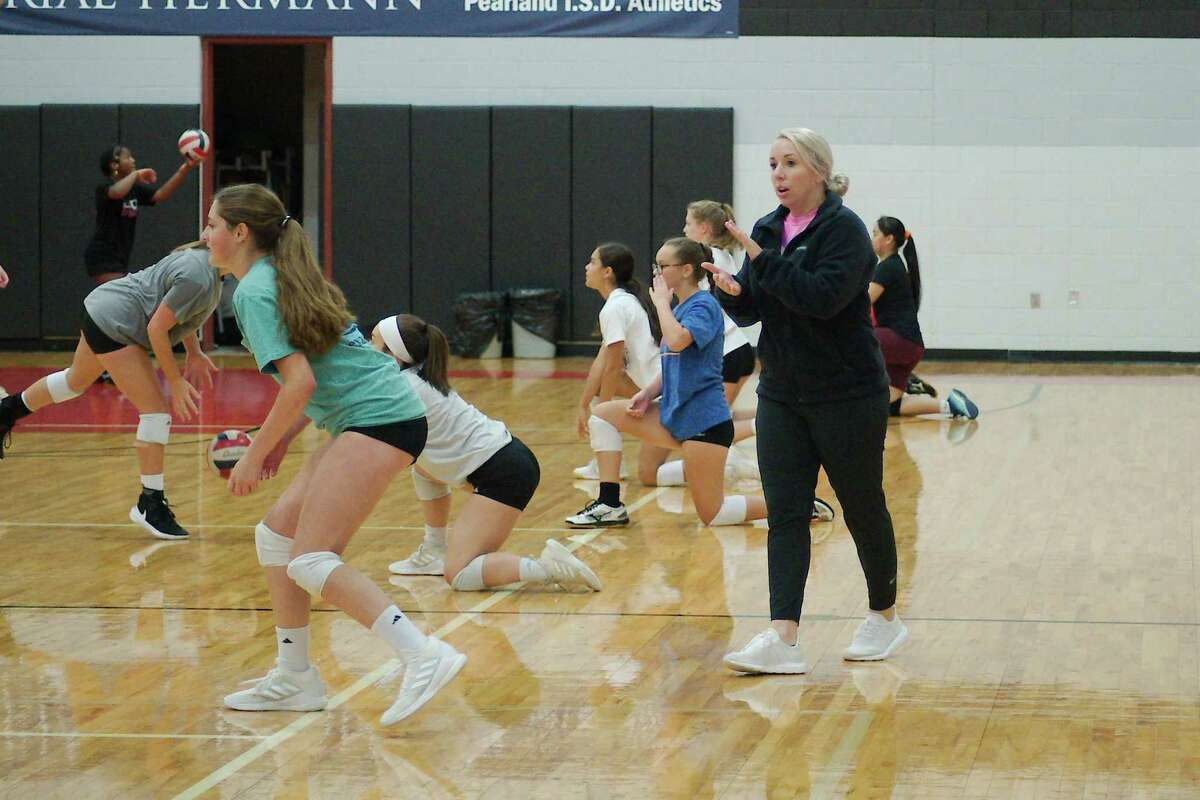 Gill observes as campers participate in hitting drill.