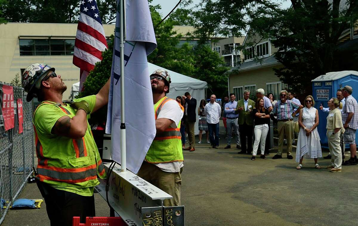 """Shawmut construction workers prepare to """"top off"""" the ironwork as HMTX Industries holds a top off reception for its new design headquarters on Tuesday, July 20, 2021, on Oakwood Ave in Norwalk, Conn. The building will be CT's """"greenest"""" commercial building when completed."""