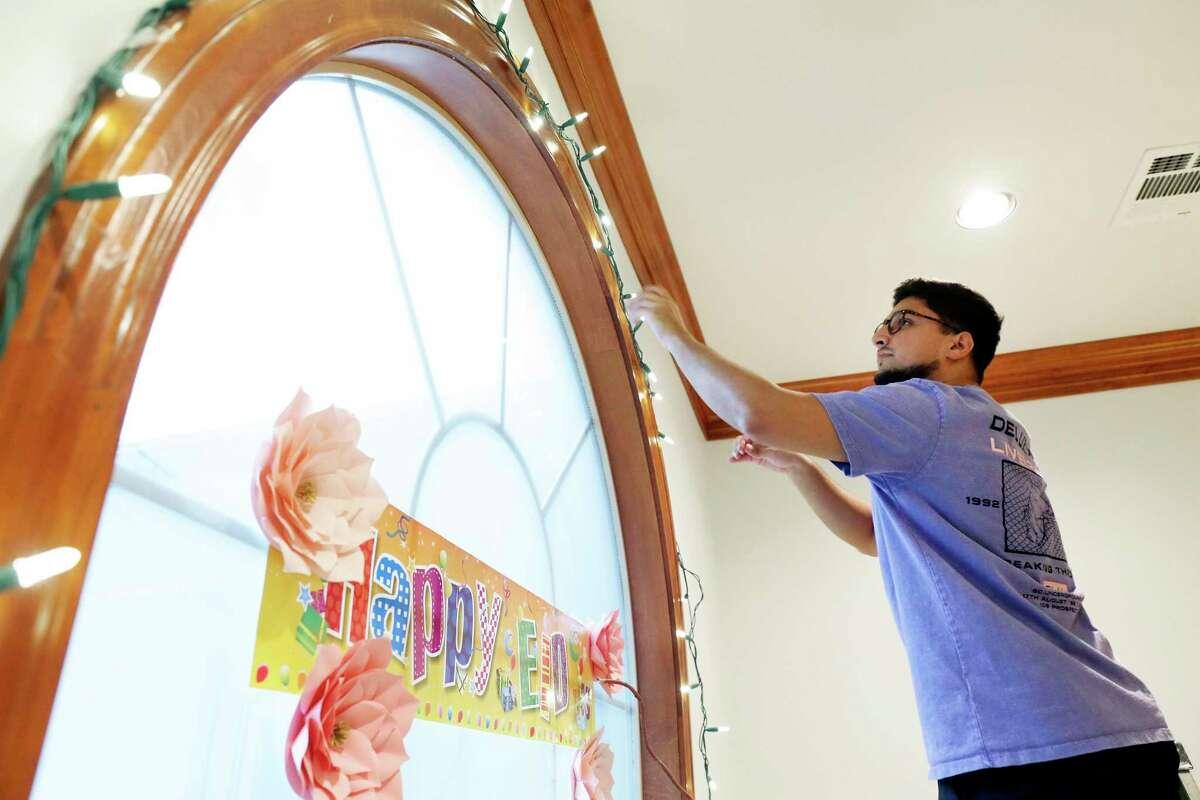 Zeeshau Shamsi hangs decorative lights in preparation for the holiday.