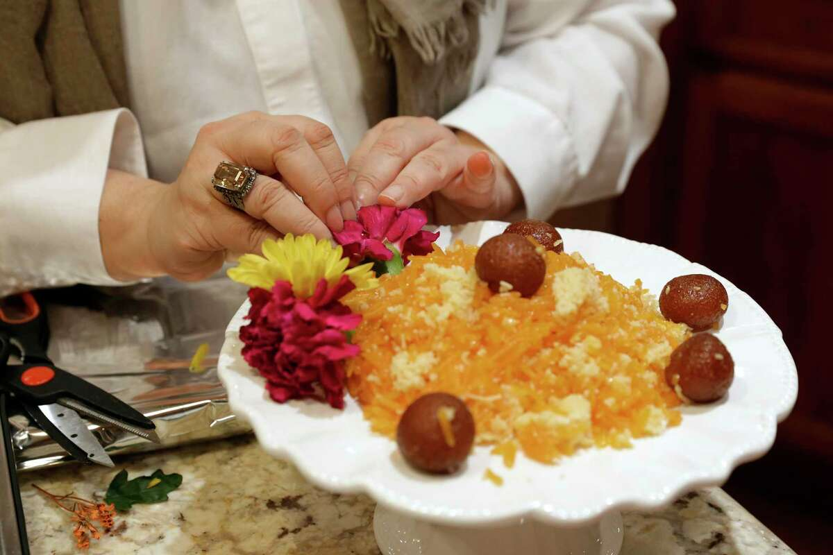 Farhat Shamsi places fresh flowers to decorate a platter of traditional zarda, a sweet rice, as the Shamsi family decorates their home dining room in preparation for the Islamic holiday of Eid al-Adha Tuesday, July 13, 2021 in Houston, TX.