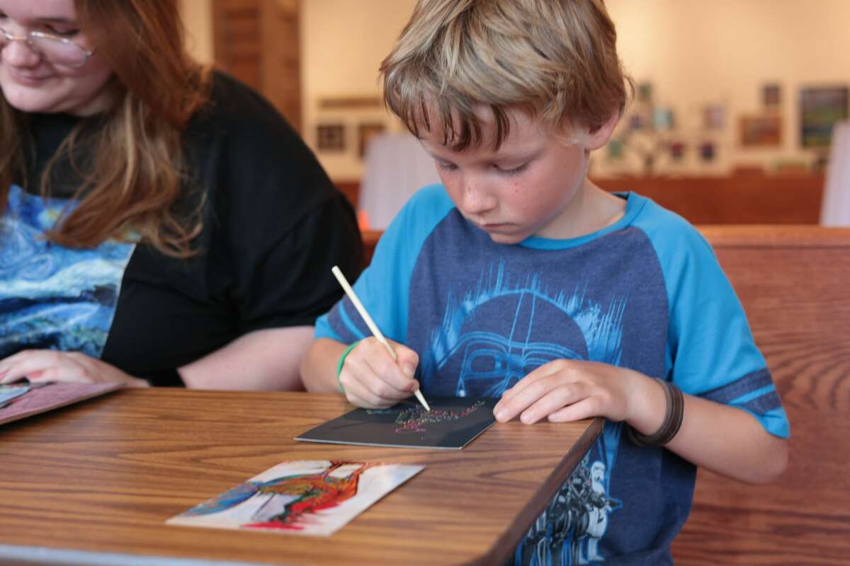 """Mathias Beboni works on replicating """"Picasso's Rooster"""" at the Picasso and a Cast of Characters workshop led by artist Lynn Williams with the help of fellow artists Anna Hansen and Mary Wahr. Beboni was part of a group of 5 children who enrolled in the class."""