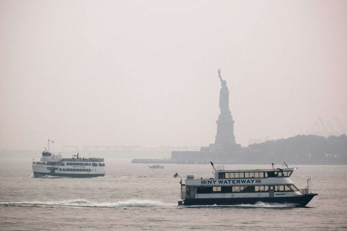 The Statue of Liberty sits behind a cloud of haze in New York City. Wildfire smoke from the West has arrived in the tri-state area, creating decreased visibility and a yellowish haze in many areas.