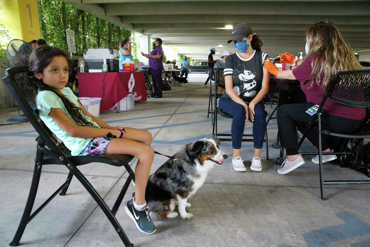 Sara Ramos receives a Covid-19 vaccination as her seven-year-old daughter, Juliana, waits with their pet dog at a pop-up clinic at the San Antonio Zoo on Tuesday, July 20, 2021. Ramos is a teacher and wanted to be vaccinated before the beginning of school. She and her husband received their first doses on Tuesday. The zoo partnered with San Antonio Metropolitan Health District to provide the public with COVID-19 vaccinations. As an incentive, the zoo gave free tickets to their Dragon Forest exhibit to everyone who received the vaccine during the event.