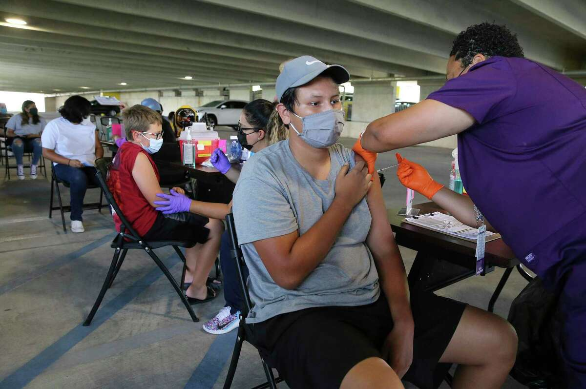 Armando Cano, 15, gets a Covid-19 vaccination from Nurse Practitioner Leslie DuBois along with other young individuals at a pop-up clinic at the San Antonio Zoo on Tuesday, July 20, 2021. Cano's 13-year-old sister, Catarina, (shown two rows back) also received her shot. Their mother, Beverly Mound, said she had heard about the pop-up clinic and since they were visiting the zoo, the opportunity arose for her children to be vaccinated before they went back to school. The zoo partnered with San Antonio Metropolitan Health District to provide the public with COVID-19 vaccinations. As an incentive, the zoo gave free tickets to their Dragon Forest exhibit to everyone who received the vaccine during the event.