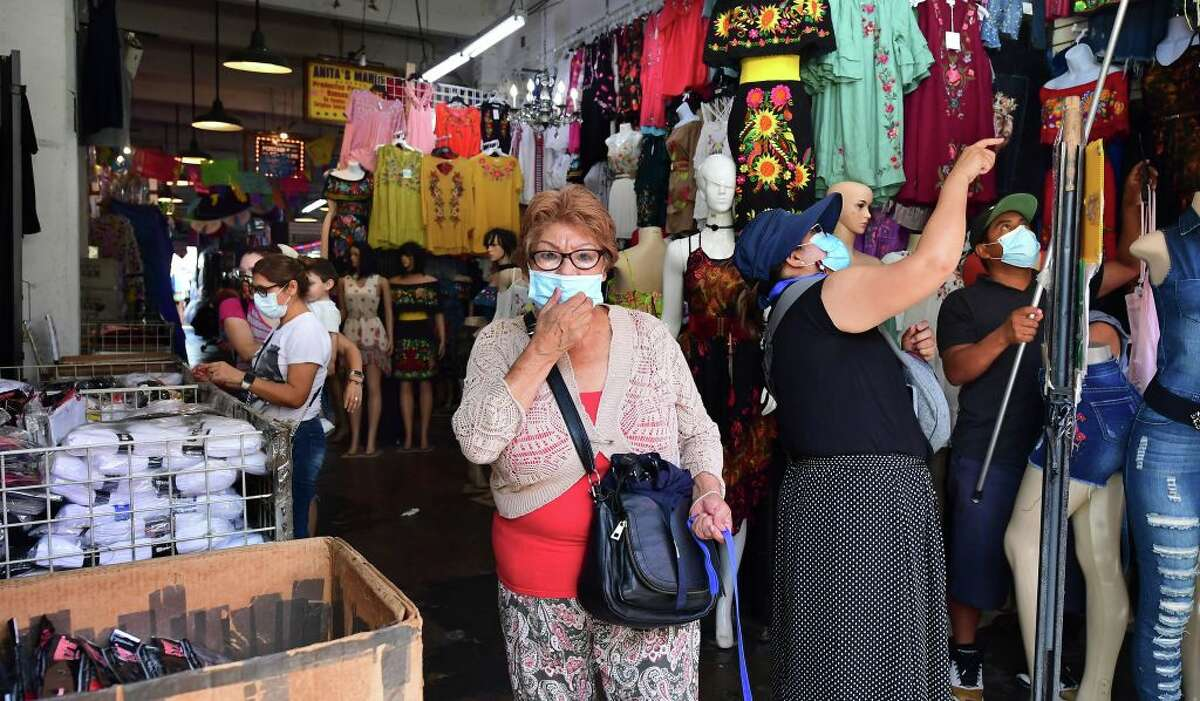 A woman adjusts her facemask while shopping in a clothing store on July 19, 2021 in Los Angeles.