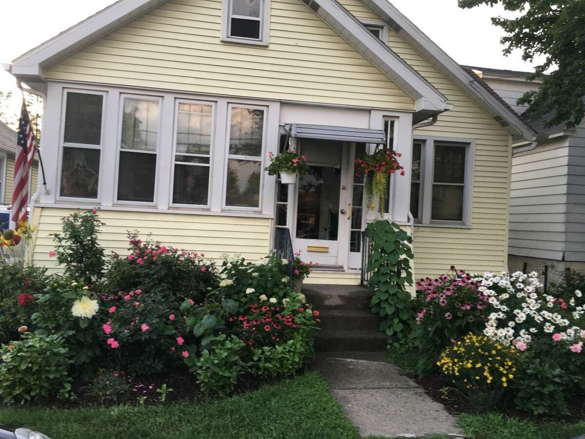 """Mary Ensslin, 94, of Colonie, a lifelong Weymouth Street resident shows the front yard of her house showing her beautiful perennial flowers. """"I spend a lot of time taking care of my flowers and receive many compliments from neighbors."""""""