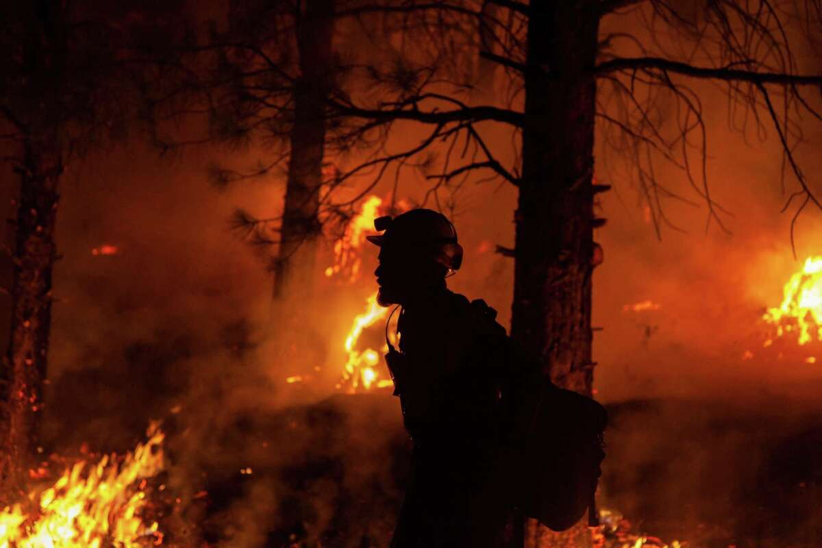 This handout photo courtesy of the U.S. Forest Service shows a firefighter during nighttime operations at the Bootleg Fire, near Klamath Falls, Oregon.