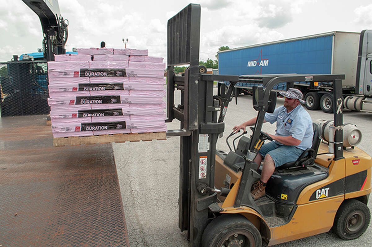 Chris Preston loads shingles onto a truck Tuesday at RP Lumber in Jacksonville. The business usually is well-stocked with shingles and other construction materials, but shortages have led to wait times on orders extending from the usual six weeks to between 10 and 14 weeks.