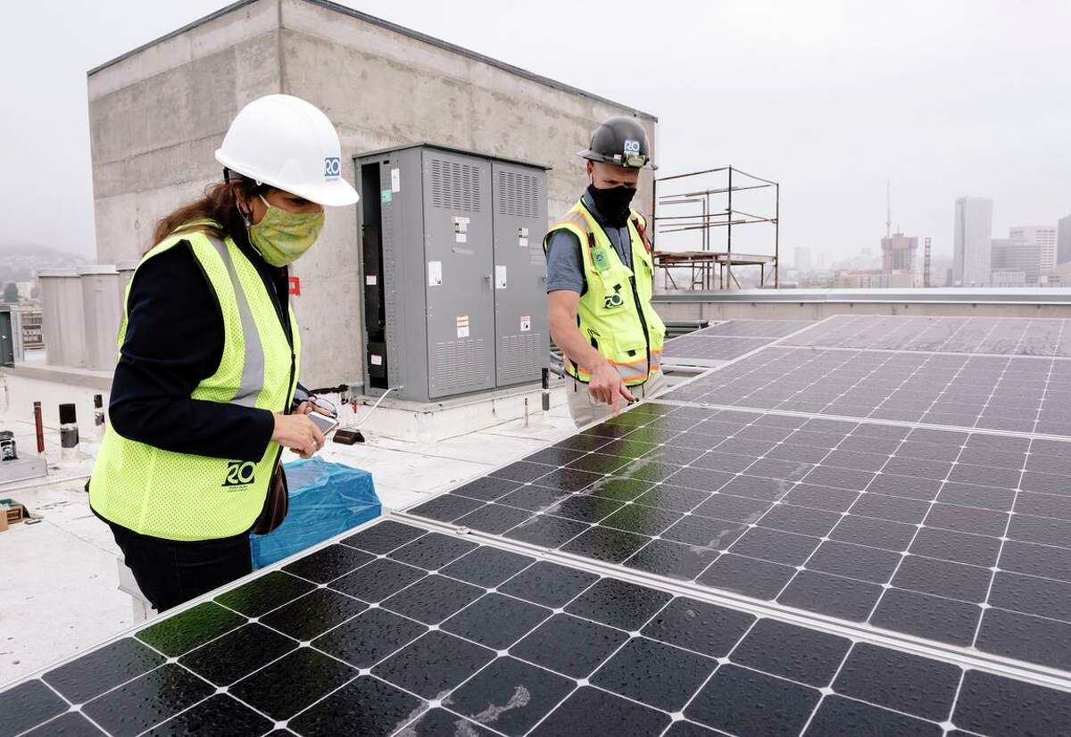 Solar panels are shown being installed on the roof of a low-income apartment in 2020. San Francisco set new, more aggressive climate change goals Tuesday, including getting to net zero greenhouse gas emissions produced in the city by 2040.