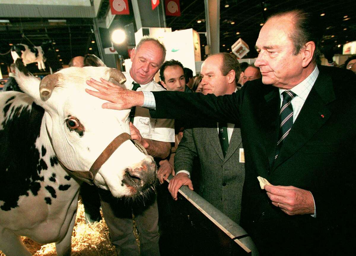 French President Jacques Chirac pets a cow while eating a piece of cheese as he inaugurates the 35th Agriculture Fair in Paris Sunday March 1, 1998.